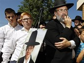 Lidé poslouchají tiskovou konferenci ke zmizení Aarona Sofera, jeho fotka je...