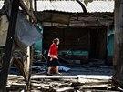 Žena prochází kolem spálených obchodů poblíž vlakového nádraží v Doněcku (30....