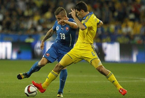 Slovák Juraj Kucka (vlevo) zasekává míč, atakuje ho Ukrajinec Taras Stěpaněnko.