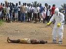 Zdravotník v Monrovii dezinfikuje tělo ležící na ulici. Nikdo neví, jestli...