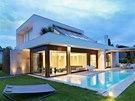 Prosklené stěny obývacího pokoje s masivními dřevěnými rámy vytvářejí zajímavý