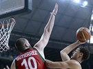 Americký basketbalista Klay Thompson (vpravo) míří na koš, vlevo ho brání...