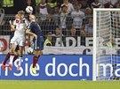 Německý fotbalista Thomas Müller (v bílém) posílá hlavou míč do sítě Skotska v...