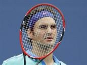 Švýcarský tenista Roger Federer skrývá hlavu za výplet rakety v semifinále US...