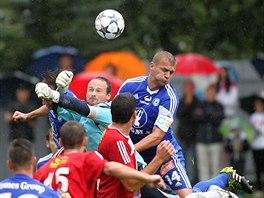 Roman Invald, brankář Velkého Meziříčí, vyráží míč před olomouckým Adamem Varadim.