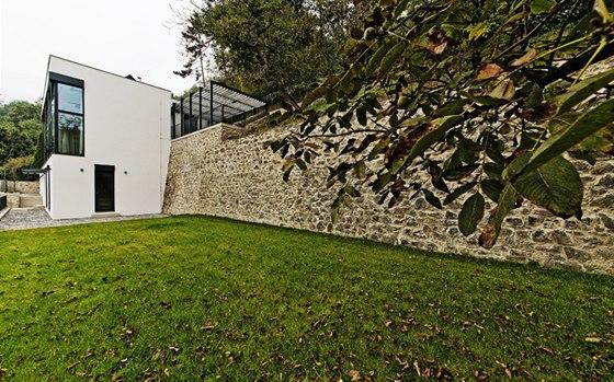 Stavba jako by vyrůstala z masivní opěrné zdi. Kontrast hladké bílé omítky a