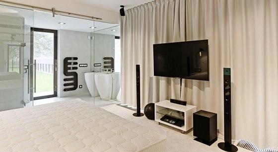 Ložnice je prosklenou stěnou přímo otevřená do koupelny. Černobílé prostředí