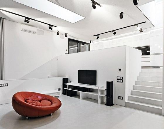 Z obývací části s vysokým stropem vede otevřené schodiště do kuchyně vybavené