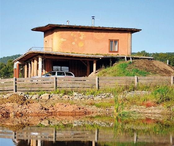 Dvoupodlažní slaměný dům s ryze přírodní dekorací na venkovní hliněné omítce.
