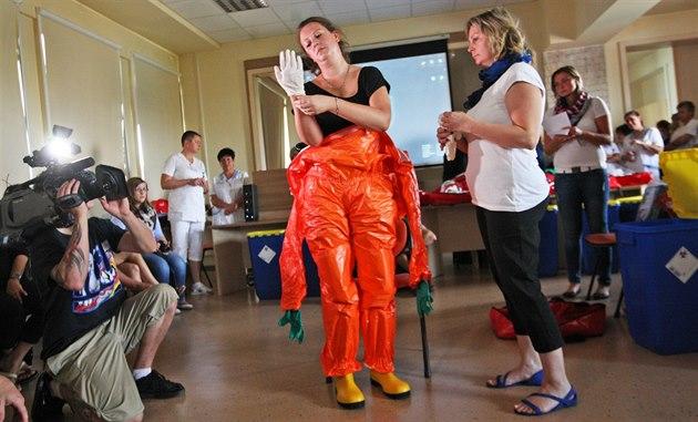Nic snadného. Zdravotníci napoprvé raději využili při oblékání pomoc asistentů.