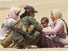 Kurdská bojovnice utěšuje jezídské ženy, které prchly před Islámským státem...