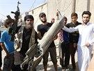 Bojovník Islámského státu ukazuje trosky syrského vládního letounu, které radikálové sestřelili v Rakká (15. září 2014)