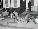 Policisté odnášejí oběti z domu DeFeových.
