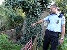 Policista ukazuje svah sesouvající se u domu Emílie a Stanislava Dostálových v...