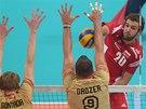 Polák Mateusz Mika smečuje v semifinále mistrovství světa, blokují ho Němci Max