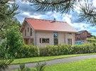 Srub se střechou Bramac a přírodní lazurou dobře zapadl mezi další rodinné domy.