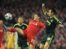 Adam Lallana (v červeném) z Liverpoolu hraje míč před Leem Tomlinem z...