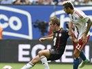 Philipp Lahm (vlevo) z Bayernu Mnichov má míč na kopačce, doráží na něj Valon...