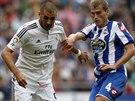 Alex Bergantinos z La Coruni (vpravo) chce vzít míč Karimu Benzemovi z Realu...