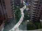 Had z odpadků se vine mezi výškovými domy v čínském městě Si-an.