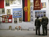 Náv�t�vníci ve uniformách NVA si prohlí�ejí fotky ze starých �as�.