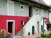 Pohled na obytnou část domu z nádvoří, kde zůstalo zachováno původní dvouramenné schodiště. Barva fasády byla zvolena tak, aby zvýraznila a podtrhla použitý  kámen v patře.