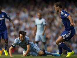 David Silva z Manchesteru City padá, na trávník ho poslal Branislav Ivanovič z