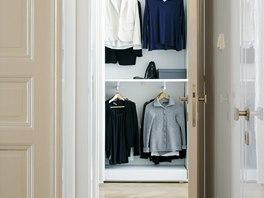 Úzká šatna s vestavěnými skříněmi a dalšími úložnými prostory ukrytými ve