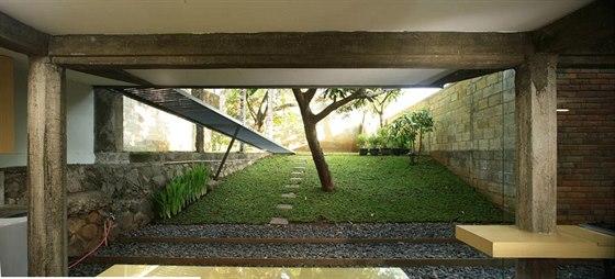 Průhled společenskou částí domu do zahrady. Architekt využil svažující pozemek ve svůj prospěch.