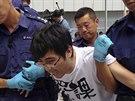 Policisté odvádějí jednoho z hlavních představitelů prodemokratického hnutí v Hongkongu Alexe Čowa (27. září 2014).