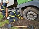 Hasiči při vyprošťování podkládali kola popelářského vozu dřevem. (6. října...