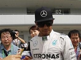 Lewis Hamilton  rozdává podpisy fanouškům v průběhu