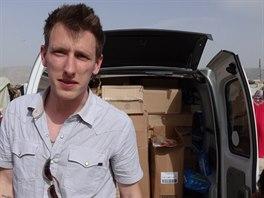 Peter Kassig na nedatovaném snímku před dodávkou naplněnou humanitární pomocí...
