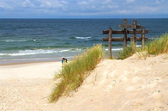 Krátká lesní spojka vedoucí kmoři ústí na pláž u velkého rozcestníku.