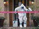 Pracovník v ochranném obleku dezinfikuje dům zdravotní sestry, která se v...