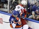 Obránce Travis Hamonic z NY Islanders tiskne na mantinel útočníka Caroliny...