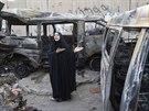 Žena ukazuje auta, která zničil sebevražedný atentátník v Bagdádu, zemřelo 45...