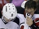 Zkrvavený útočník  Martin Havlat z New Jersey opouští led za pomoci spoluhráče...