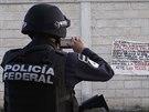 Mexický policista z federálních jednotek si fotí banner na zdi ve městě Iguala, na kterém se píše o obavě, že v Iguale začne zabíjení, pokud tam nebudou žádní policisté. Celkem 22 policistů bylo zatčeno kvůli podezření ze střelby na autobus se studenty.