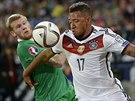 Německý fotbalista Jerome Boateng (vpravo) si kryje míč před Jamesem McCleanem...