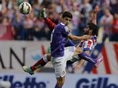VE VZDUCHU. Raul García z Atlétika Madrid akrobaticky odkopává míč, tísní ho