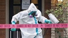 Pracovník v ochranném obleku dezinfikuje d�m zdravotní sestry, která se v...