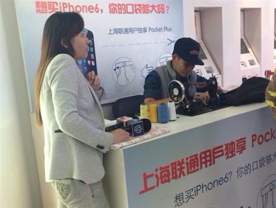 Krejčí přešívá v šanghajském obchodě China Unikom kapsy kalhot pro přenášení...
