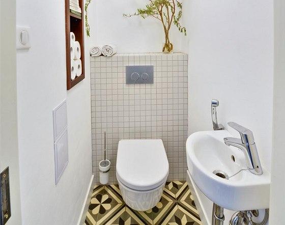 Replika historické dlažby je použita také na toaletě. Klozet (Ideal Standard) doplňuje bidetová sprška (Hansgrohe) a malé umyvadlo (Ideal Standard).
