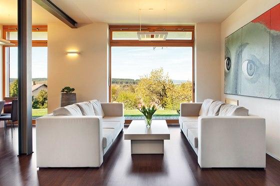 Velkoplošná okna nabízejí výhled na Kleť a Blanský les. Přehřívání interiéru prosklenou plochou brání přesahy střechy.