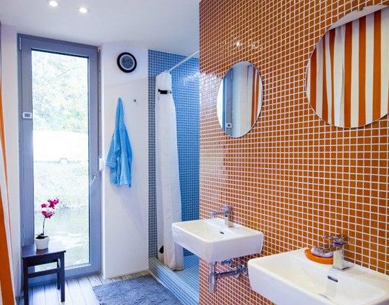 I V koupelně jsou dvě umyvadla a velký sprchový kout, skleněná mozaika opakuje barevnost použitou na celém hausbótu.