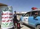"""Členové Hútíů na kontrolním stanovišti v Sanaa, na nápise je napsáno: """"Alláh je velký, smrt Americe, smrt Izraeli, prokletí na židy, vítězství islámu (16. října 2014)."""