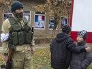 Děti v blízkosti proruského ozbrojence v městě Novoazovsk.