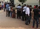 Lidé čekají ve frontě před volební místností.