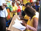 Lidé u volebních uren nechávají ověřovat svou totožnost.